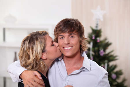 a young woman kissing a young man in front of a Christmas tree photo