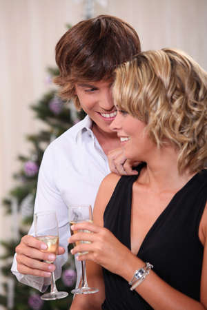 Intimate young couple drinking champagne at Christmas photo