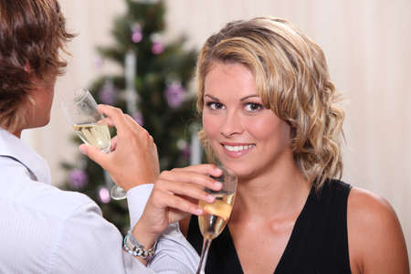 entwined: Pretty young woman drinking champagne with her boyfriend at Christmas Stock Photo