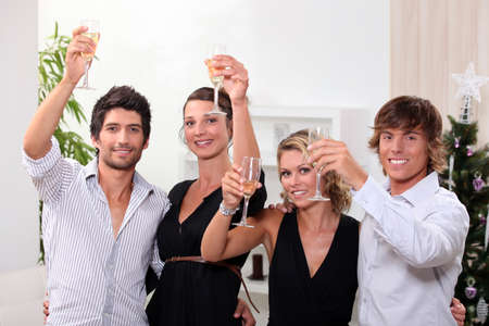 Two young couples drinking champagne at Christmas photo