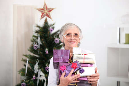Old woman holding Christmas presents photo