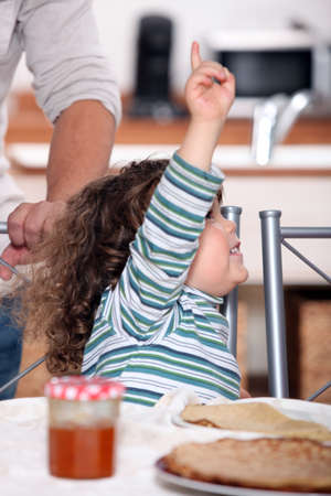 permission: toddler raising arm to ask for permission Stock Photo