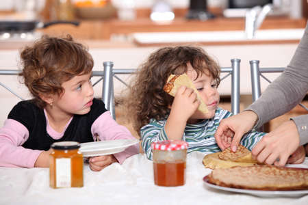 Two children at kitchen table having breakfast photo
