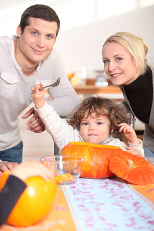 a little child  eating a pumpkin and his parents Stock Photo - 13905619