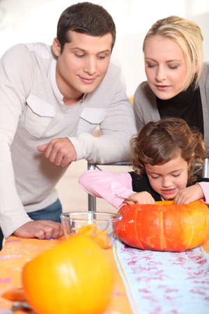 Little girl and parents carving pumpkin for Halloween photo