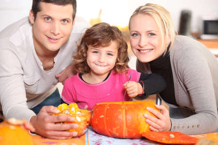 A family carving a pumpkin. photo