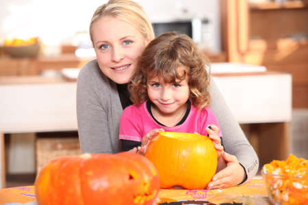 Mother and daughter decorating pumpkins photo