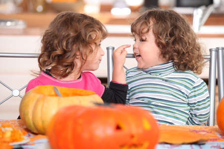 Children carving Halloween pumpkins photo