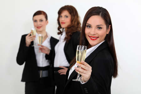 Young women in smart suit with glasses of champagne photo