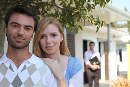 purchasers: portrait of young couple with realtor in background