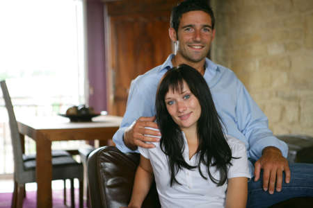 facing to camera: Young couple smiling sitting in an armchair Stock Photo
