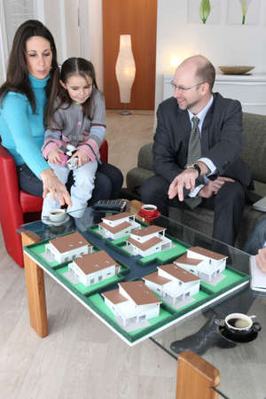 Architect showing model housing to mother and daughter photo