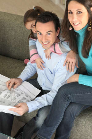 Young family relaxing on sofa with newspaper Stock Photo - 13914048