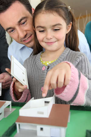 new build: Little girl playing with scale model of housing