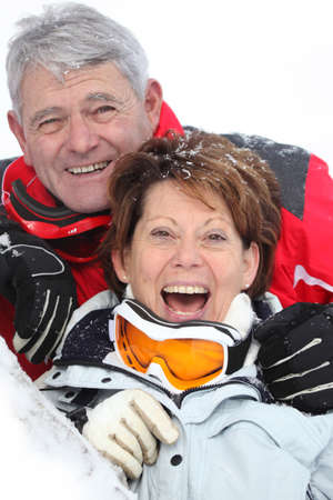 Senior couple having a great time skiing photo