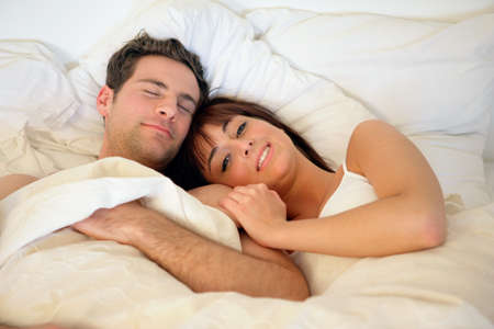 Happy couple lying in bed photo