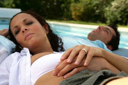 recliner: Couple lying by a pool Stock Photo