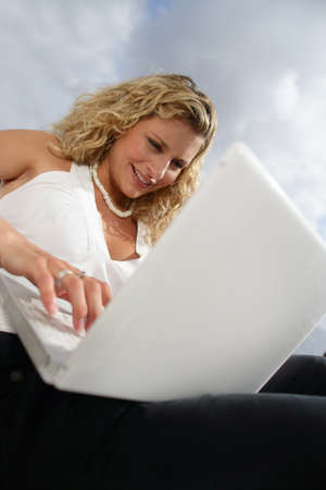 Young woman using her laptop outdoors photo
