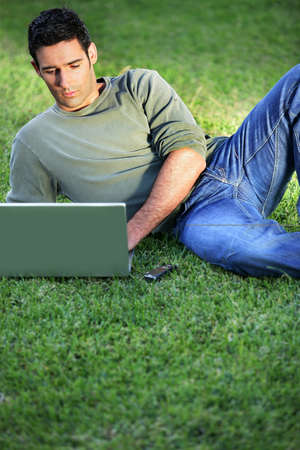 Man lying on the grass in front of laptop photo