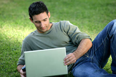 Man using his laptop on the grass photo