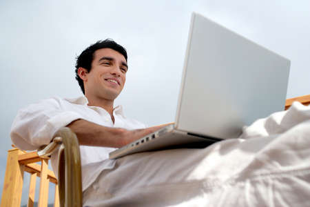 Man sat on garden chair with laptop photo