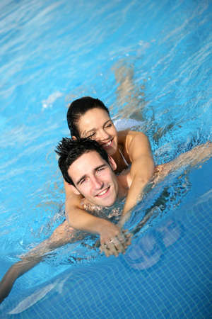 Happy couple in a swimming pool photo