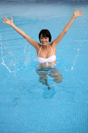 Brunette jumping in swimming pool photo