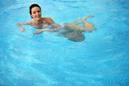 Brunette taking a dip in the pool Stock Photo - 13915745