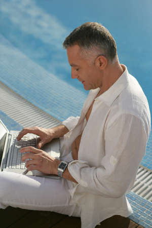 unbuttoned: middle-aged gentleman sitting on swimming pool edge with laptop Stock Photo