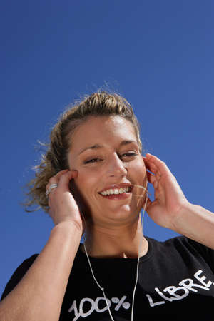 Blond woman listening to music in the sun photo