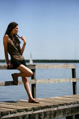 Contemplative brunette stood on jetty photo
