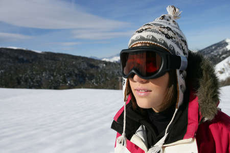 A young skier wearing a pair of goggles on a sunny day Stock Photo - 13914905