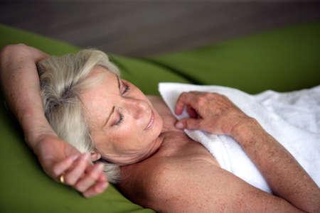 sleep well: Senior woman asleep in a towel Stock Photo