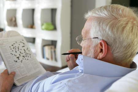 crosswords: Senior man doing crossword