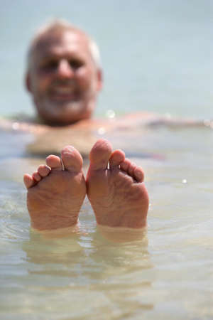 poking: Man poking his feet out of the water Stock Photo