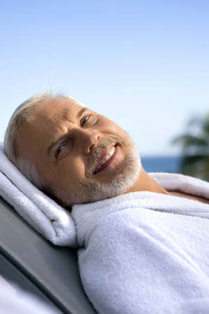 Grey-haired man on sun lounger photo