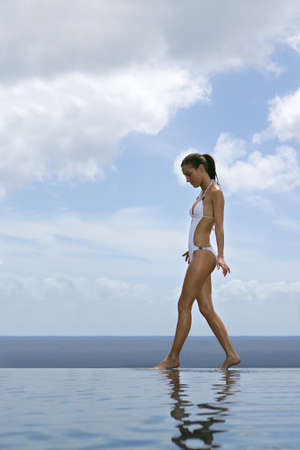 Woman walking along an infinity pool photo
