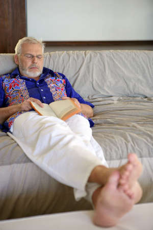 senior holding a book and sleeping on the couch photo