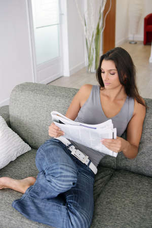attractive couch: Woman reading the paper