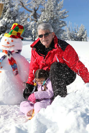 Father and grandfather building snowman photo