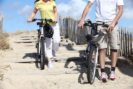 firmeza: hombre y una mujer andar en bicicleta en la playa Foto de archivo