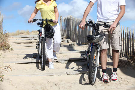 young man and woman riding bikes on the beach photo
