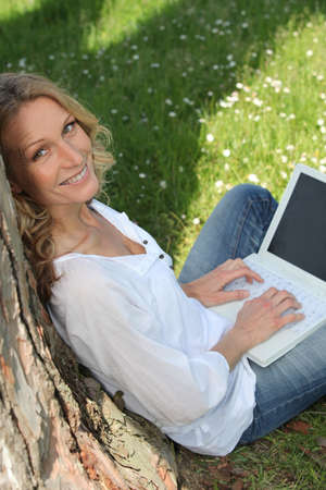 portrait of beautiful blonde leaning against tree working on laptop