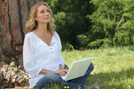 donna pensiero: Donna bionda sedeva accanto albero con laptop assorto nei suoi pensieri Archivio Fotografico