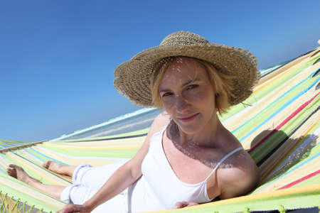 Blond woman relaxing at the beach in hammock photo