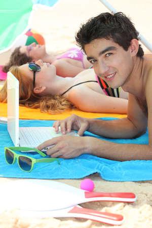 Boy on beach with computer photo