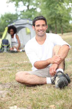 a man seated, behind him, a canvas tent and a woman photo