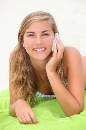 Blond teenager laying on a beach whilst making a call photo