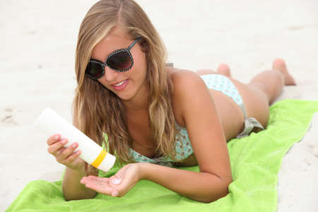 short back: Woman on the beach with suncream Stock Photo