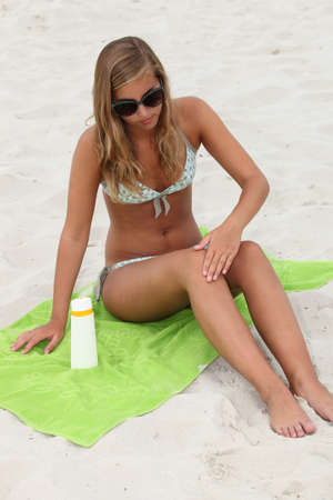 strand of hair: Young woman applying sunblock at the beach